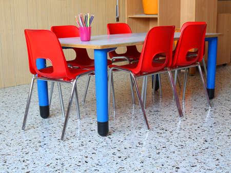 day care center: interiot classroom of a kindergarten with red chairs and small school tables Stock Photo