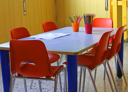 day care center: classroom of a kindergarten with red chairs and small desks and lots of colored pencils Stock Photo