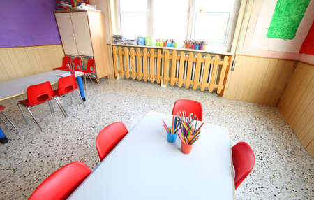scholastic: classroom of kindergarten with desks and small red chairs