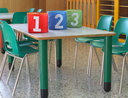 day care center: containers with large numbers on the desk in the kindergarten
