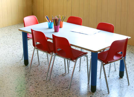school room: desk of a nursery school with pencils and small red chairs Stock Photo