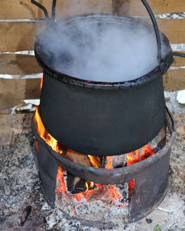 vaporize: black pot with the fire and the white smoke during cooking