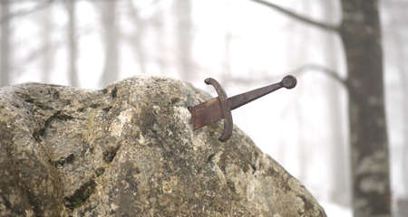 legendary: legendary Excalibur sword into the stone in the middle of the forest in winter