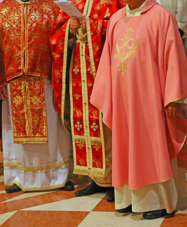 liturgical: many priests with pink cassock in church during the celebration of Holy Mass
