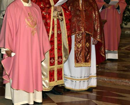 sotana: muchos sacerdotes con sotana de color rosa en la iglesia durante la celebración de la misa Foto de archivo