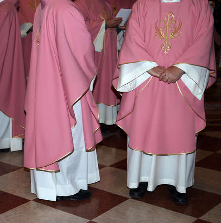 priests: priests with pink cassock in church during the Holy Mass Stock Photo