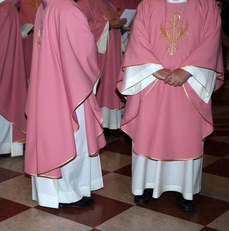 sotana: sacerdotes con sotana de color rosa en la iglesia durante la misa