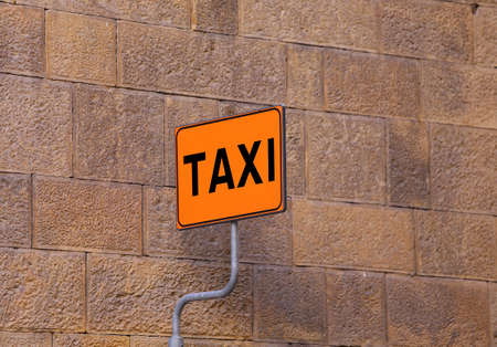 taxi sign: TAXI sign on the taxi stop with a wall of an old building as background