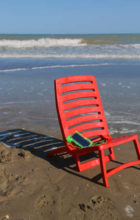 stillness: chair on the beach by the ocean wave and a smartphone Stock Photo