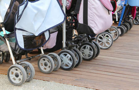 population growth: many wheels of strollers for toddlers parked on the wooden parquet floor