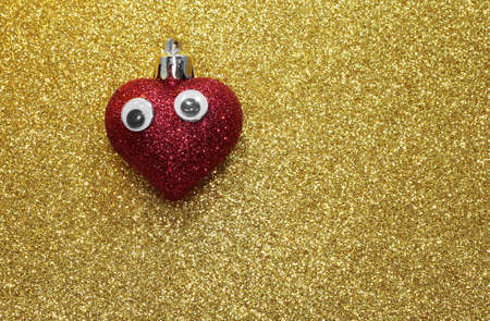 twinkles: isolated red heart with eyes on the golden background shiny
