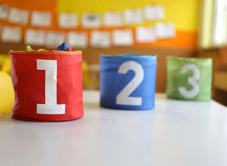 three children: Three jars colored Red Green and blue with written one two and three in the kindergarten classroom