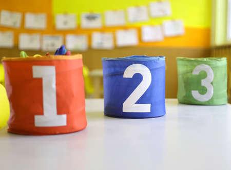 école maternelle: Red pots bleus verts avec le grand lettrage un deux et trois sur la table dans la classe de maternelle