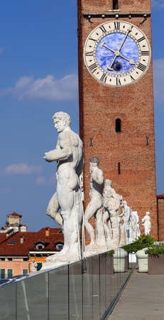 clocktower: Vicenza, Italy. Ancient white stone statues of people over the Basilica Palladiana and the big clock tower Stock Photo