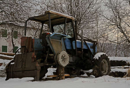rummage: abandoned tractor without a wheel in the snow in winter