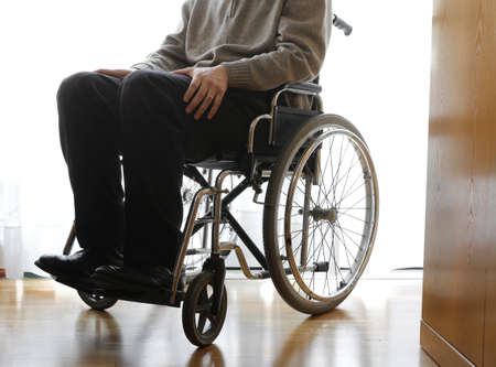 dystrophy: disabled elderly sitting in a wheelchair in the his room Stock Photo