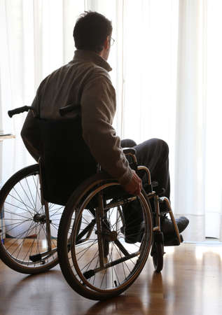 disabled sitting in a wheelchair in the room in front of the window Stock Photo