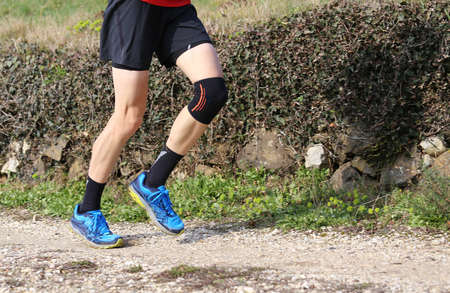 runner during the cross-country race with his knee wrapped by a knee brace Stock Photo