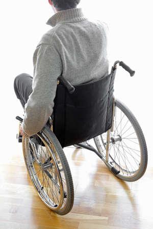 personas discapacitadas: hombre discapacitado en silla de ruedas en la sala frente a la ventana Foto de archivo