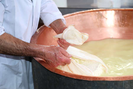 whey: Senior expert cheesemaker collects the cheese with the tarp from the large copper cauldron filled with milk and whey