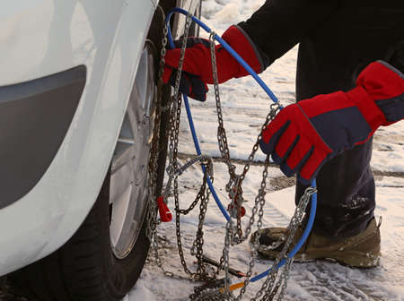 pneumatic tyres: man with red gloves install snow chains in the car tyre in winter