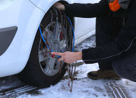chagrin: automobile mechanic mounting snow chains in the car tyre in winter on snow