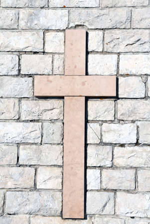 religiosity: symbol of the cross carved on marble attached to the stone wall in vertical