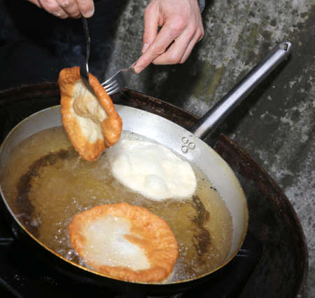 fritters: Cook hands during preparation of fritters in very hot oil Stock Photo