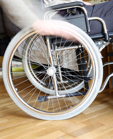 dystrophy: hand of the young disabled in the wheel of the wheelchair