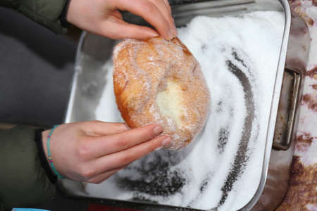 street vendor: hands of young street vendor while spreading sugar on freshly fried hot fritter Stock Photo