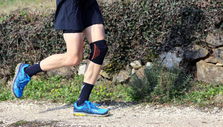 cross-country runner during the race with his knee wrapped by a knee brace Stock Photo