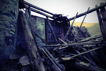 outburst: wooden planks and rubble and the ruins of the house completely destroyed by powerful earthquake