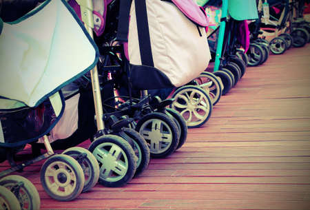 population growth: many strollers for toddlers parked on the parquet floor of wood
