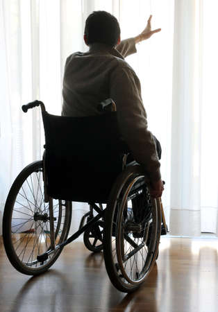 infirm: disabled sitting in a wheelchair in the room in front of the window Stock Photo
