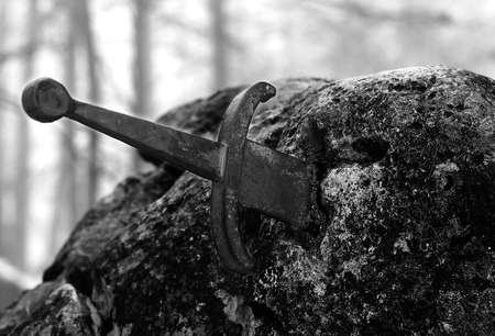 legendary Excalibur sword into the stone in the middle of the forest in winter