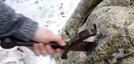 rapier: Hand of the valiant knight in moviment tries to remove the magical Excalibur sword in the stone Stock Photo