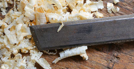 carpenter's sawdust: Blade of a sharpened chisel and sawdust in the Carpenters Workbench