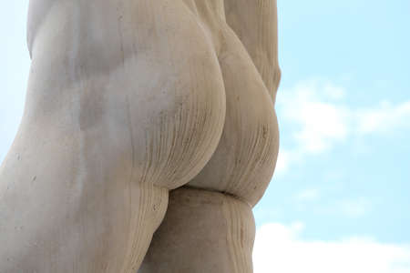 detail of the back of the marble statue with white buttocks