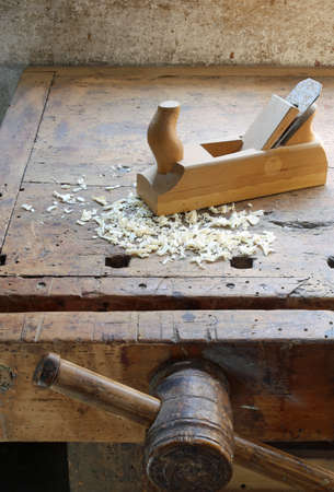 carpenter vise: Planer shavings and sawdust in an antique wooden Workbench with vise inside the craftsman joinery manufacturer