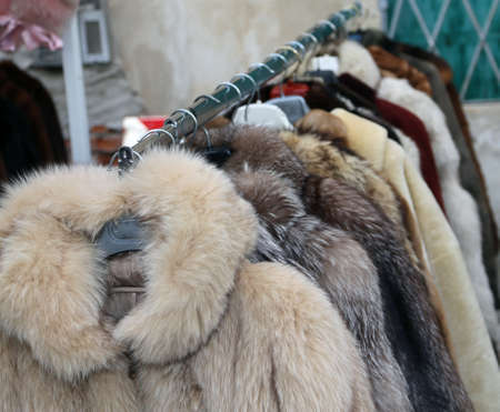 valuable: many valuable fur coat in vintage style for sale in the flea market outdoors