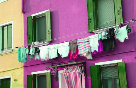 launderette: just washed laundry and lots of clothes hung out to dry in the italian town Stock Photo