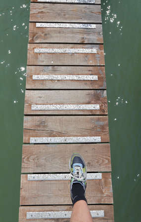 tennis shoe: foot of the boy with the tennis shoe above the walkway in the middle of the water of the sea Stock Photo
