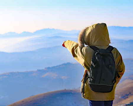 admires: young Explorer with Backpack admires the panorama from the top of a mountain in winter
