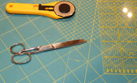 millimeter: cutter and scissors on the worktop with millimeter scale background of a company to create fashionable clothes