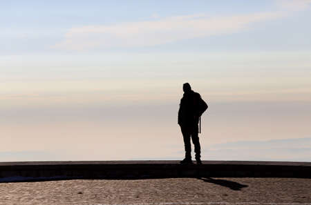 admires: man in backlight admires the view from the top of a mountain