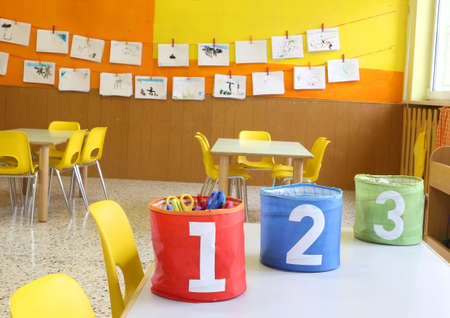 kiddy: Red Green and blue jars with large lettering one two and three on the table in the kindergarten class