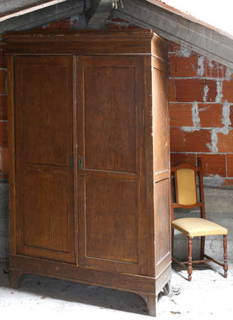 abandonment: antique wooden wardrobe in the dusty attic and an old chair