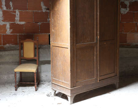 wooden wardrobe in the dusty attic and a chair