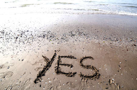 sand writing: Great writing on the sand of the sea with the word YES