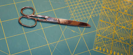millimeter: large tailors scissors on the worktop with millimeter scale background of a company to create fashionable clothes